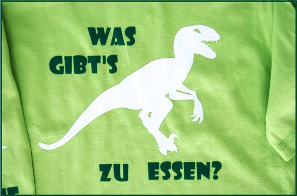 """Hellgrünes T-Shirt mit Motiv Dino. Zeichnung eines Dinosauriers und dem Text """"Was gibt's zu essen?"""""""
