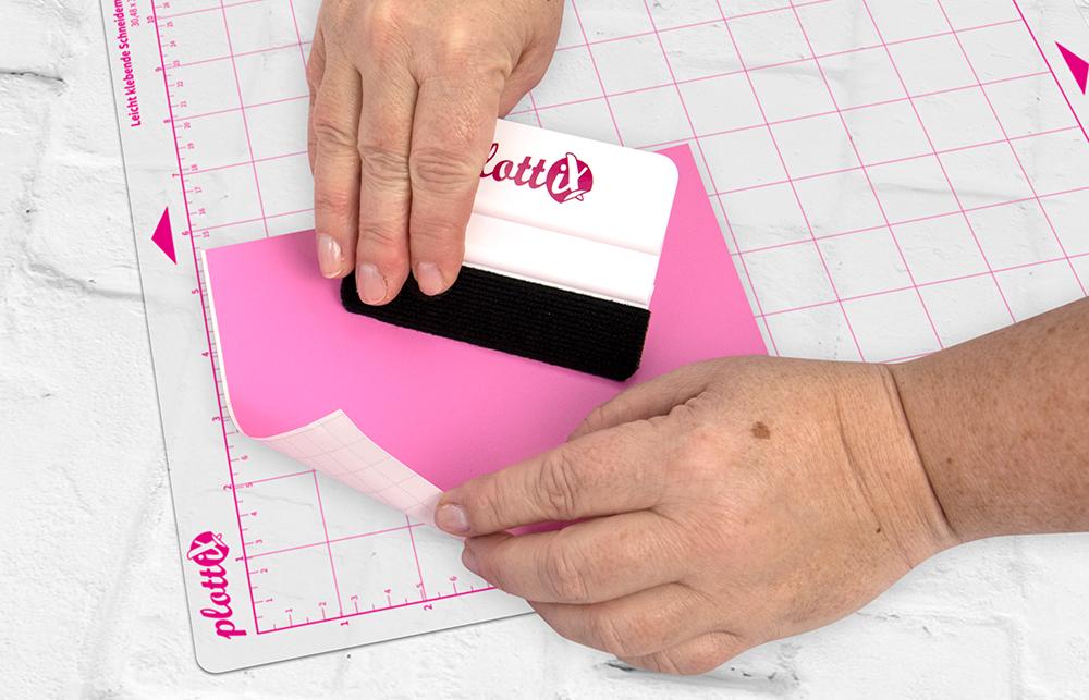 Legen Sie nun Ihr Material auf Ihre Schneidematte. Das Trägerpapier zeigt hier nach unten und Ihre Folie nach oben.